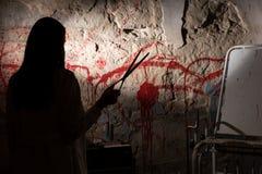 De schaduwrijke vrouwelijke schaar van de cijferholding dichtbij bloedvlekke muur royalty-vrije stock foto's