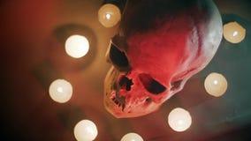 De schedel in de cirkel van kaarsen, op een mistige achtergrond stock footage