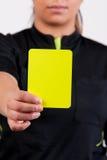 De scheidsrechter die van het voetbal de gele kaart toont Stock Foto's