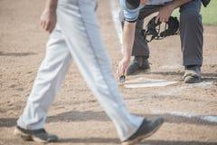 De scheidsrechter maakt huisplaat, speler in voorgrond schoon stock foto