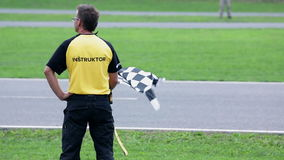 De scheidsrechter met een geruite vlag bevindt zich aan de kant van het gaan-kar het rennen spoor stock video