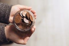 De schenkingskruik van de vrouwenholding met muntstukken op lichte achtergrond, hoogste mening royalty-vrije stock foto