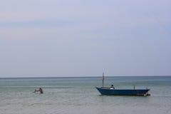 De Schepen en de boot van de visserszonsopgang op het strand Stock Foto