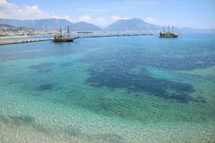 De schepen op het blauwe overzees die in de afstand bij de rotsen varen stock foto's