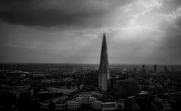 De Scherf Londen met stralen die van zon door een stormachtige hemel barsten royalty-vrije stock foto