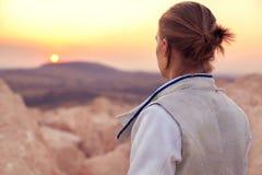 De schermermens op zich de rotsachtige achtergrond en het verheugen op de zon daalt Stock Foto