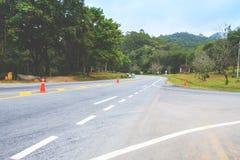 De scherpe kromme van de asfaltweg samen met tropisch bos, stock foto's
