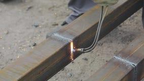 De scherpe metaalproducten met een gassnijder, de arbeider snijdt het metaalprofiel met een gassnijder, snijdt metaalclose-up