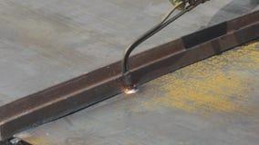 De scherpe metaalproducten met een gassnijder, de arbeider snijdt een metaalblad met een gassnijder, het close-up van het besnoei