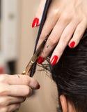 De scherpe schaar van het mensen` s haar in een schoonheidssalon stock foto's