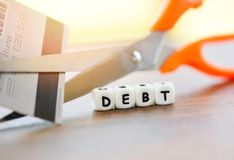 De scherpe schuld/de Gesneden creditcard met schaar voor einde om geld te betalen beschermt kosten financiële crisis stock afbeelding