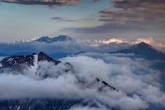 De scherpe van piekenkaravanke de waaier en van Kamnik stijging van Alpen boven wolken Stock Fotografie