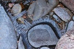 De scherven van ijs groeien naar buiten op rivierrotsen Stock Foto