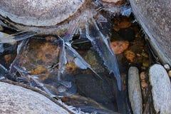 De scherven van ijs met iriserende glans groeien op rivierrotsen Stock Afbeeldingen