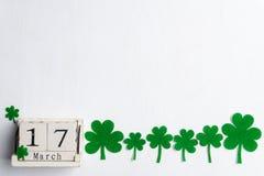 De scheurkalender voor St Patrick Dag, 17 Maart, met groen klaverblad, groen water en document etiketteert op witte houten achter stock foto's