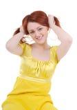 De schichtige spelen van de jonge vrouw met haar rood haar Stock Afbeelding