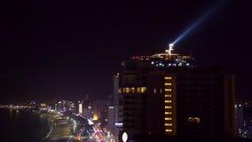 De schijnwerper op het dak van een wolkenkrabber glanst in de nachthemel stock footage