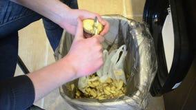 de schilaardappel van mensenhanden het knippen van daling in afvalbak stock videobeelden