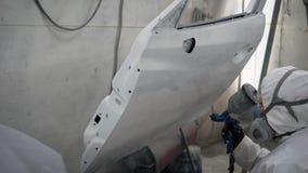 De schilder behandelt autodeur door witte verf van spuitpistool in een winkel van de autodienst na reparatie stock footage