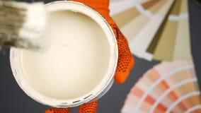 De schilder houdt een blik met beige verf en dompelt de borstel in het onder Langzame Motie stock video