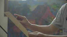 De schilder houdt een canvas en maakt het schilderen stock videobeelden