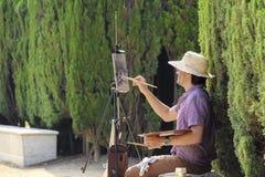 De schilder zit in ciudadelapark van Barcelona onder groene installaties Royalty-vrije Stock Afbeeldingen