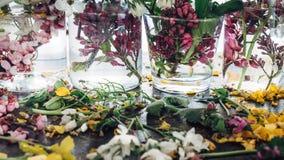 De schilderachtige boeketten van de kleurrijke lente bloeit in de flessen van glasvazen, die zich op een rij op een lichte houten Stock Foto