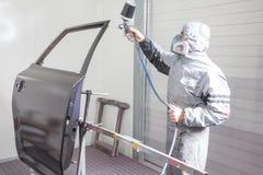 De schilders bespuitende verf van het autolichaam op carrosseriedelen Stock Afbeelding