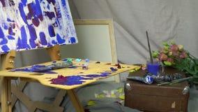 De schilders` s werkplaats, een houten palet in olieverven, canvas, verven en borstels Er zijn rond bloemen allen stock videobeelden