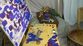 De schilders` s werkplaats, een houten schildersezel, een canvas met een niet gemarkeerd beeld, de borstels en de verven liggen o stock footage