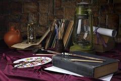 De schildersezel met borstels ligt op de lijst dichtbij de oude olielamp Gestileerd als retro stilleven Selectieve nadruk Stock Fotografie