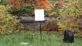 De schildersezel, de zwarte rugzak en de verven bevinden zich op het gras in het de herfstpark stock afbeeldingen