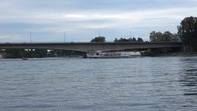 De schipzeilen met mensen op de rivier onder de brug stock video