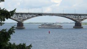 De schipzeilen onder de brug de rivier van Saratov-Engels, Volga, Rusland stock footage