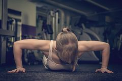 De schitterende blondevrouw die en wat opwarmen doen duwt UPS de gymnastiek, de gezonde levensstijl van het Sportenconcept en de  royalty-vrije stock foto