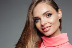 De schitterende blondevrouw in roze sweater met golvend volumed haar stock afbeelding