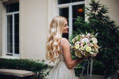 De schitterende bruid met huwelijk bloeit boquet in openlucht het stellen, tegen luxehuis royalty-vrije stock afbeelding