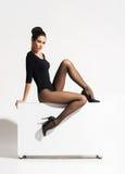 De schitterende dame die met hete benen in sexy zitten stelt op een kubus Stock Afbeeldingen