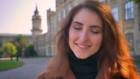 De schitterende donkerbruine Kaukasische vrouw kijkt dicht omhoog naar camera en shillind in stedelijk gebied dichtbij oude gebou stock video