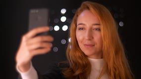 De schitterende gember Kaukasische vrouw houdt telefoon en neemt selfies terwijl status in zwarte studio, verrukkelijke lengte stock videobeelden
