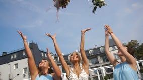 De schitterende glimlachende blondebruid en haar mooie bruidsmeisjes werpen in de boeketten van het luchthuwelijk en vangen dicht stock footage