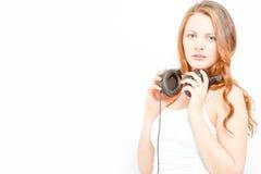 De schitterende jonge vrouw houdt hoofdtelefoons Stock Foto