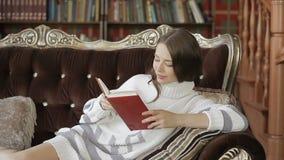 De schitterende jonge vrouw leest een boek, terwijl het liggen op een luxebank stock videobeelden