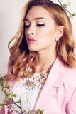 De schitterende jonge vrouw met blond krullend haar draagt elegant kostuum en juweel Royalty-vrije Stock Fotografie