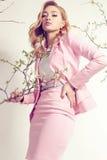 De schitterende jonge vrouw met blond krullend haar draagt elegant kostuum en juweel Royalty-vrije Stock Foto