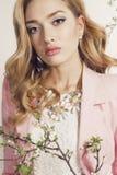 De schitterende jonge vrouw met blond krullend haar draagt elegant kostuum en juweel Stock Foto