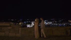 De schitterende jonggehuwden op de stad overbruggen bij nacht De zitting van het nachthuwelijk stock videobeelden