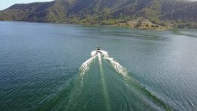 De schitterende 4k luchthommelmening over persoonswater die maakte aan motorboot vast in het tropische oceaanzeegezicht van de be stock footage