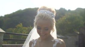 De schitterende modieuze bruid met charmante glimlach loopt langs de bloeiende tuin tijdens de zonsondergang stock video