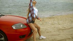 De schitterende slanke dame zit op een rode auto op een strand stock video